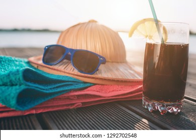 Glass of cola on wooden pier. Colorful towels lying. Sunglasses on hat. Sun shining. Beautiful nature.