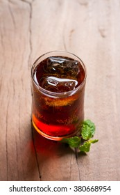 glass of cola poured to the brim with ice and mint on a wooden table closeup. Free space for text. Selective focus. Copy space