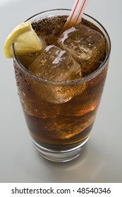 Glass of cola with straws and ice and lemon