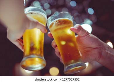glass of cold beer bottoms up with beautiful bokeh, friends drink beer together, retro tone