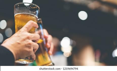 glass of cold beer bottoms up, friends drink beer together