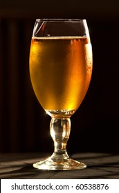 Glass of cold beer covered in condensation droplets.