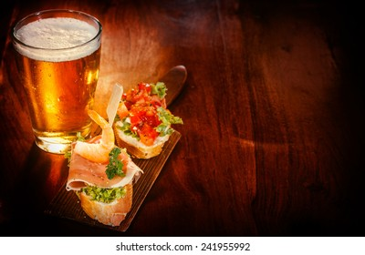 Glass of cold beer with delicious tapas topped with shrimp, parma ham and tomato on baguette served on a wooden bar or pub counter for tasty snacks