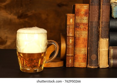 Glass of cold beer and old books. Rest with the book