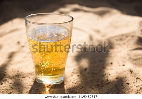 a glass of Cold beer on the beach sand, summer vacation concept