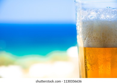 Glass of cold beer on blurred aegean sea background, Greece.