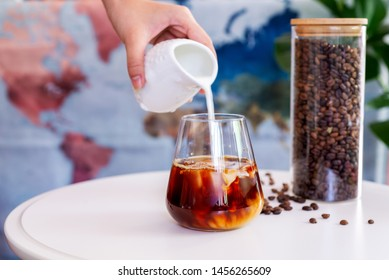 a glass of cold brew coffee with milk on white table
