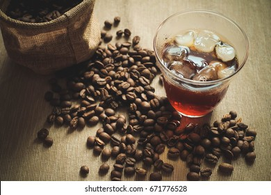 A glass of cold brewed coffee with coffee bean on the ground