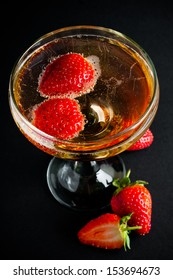 Glass of cold champagne with strawberries on a black background, close-up