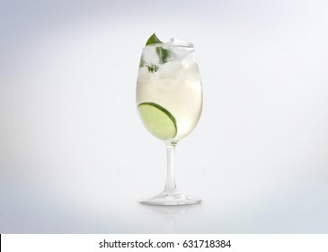 Glass of a cold cocktail drink with white wine / vermouth, slice of lemon / lime and a mint leaf. Isolated on white background.