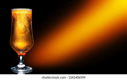 Glass of cold craft light beer on dark background.