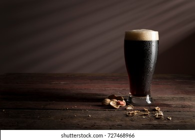 Glass of cold dark beer with foam placed on a rustic wooden table with a some peanuts next to it
