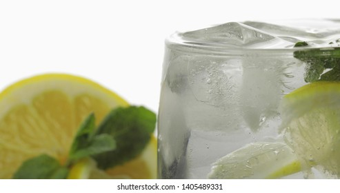 Glass with a cold drink with leaves of mint, lime, lemon and ice cubes. Releasing bubbles and foaming in sparkling water. Aerated water in glass on white background