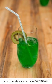 a glass of cold fresh green drink on the wooden bar, cocktail with kiwi