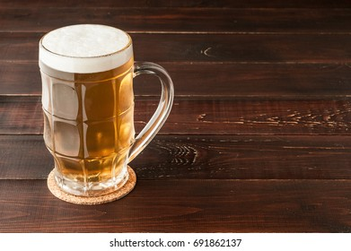 glass of cold frothy lager beer and potato chips plate on an old wooden table