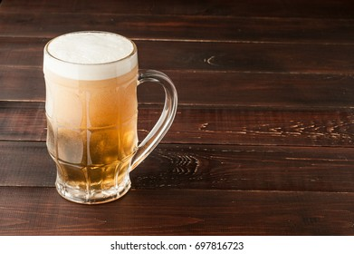 glass of cold frothy lager beer on an old wooden table