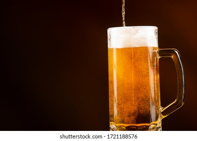Glass of cold golden beer isolated on a black background
