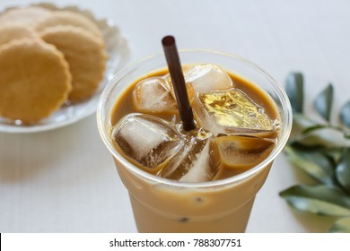 Glass of cold iced coffee with craker in small plate.