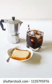 glass of cold iced coffee with homemade butter cake on white table.