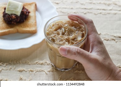 Glass of cold iced coffee on cloth background.