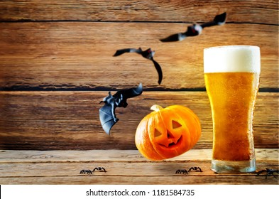 Glass of cold light beer with flying bats and pumpkin on a wood background for Halloween. toning. selective focus