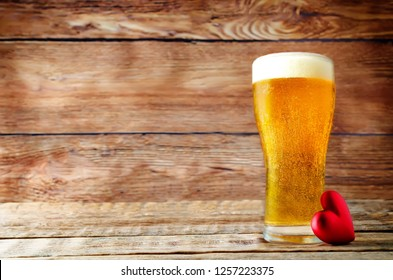Glass of cold light beer with heart on a wood background for Valentine's day. toning. selective focus