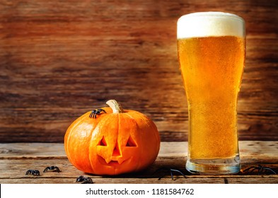 Glass of cold light beer with pumpkin on a wood background for Halloween. toning. selective focus