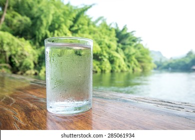 Glass of cold mineral water on the table of the natural background