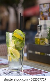 A glass of cold mint lemonade with lemon and lime