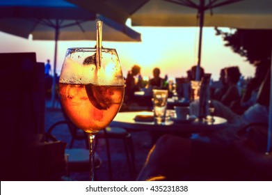 A glass of cold orange cocktail at the sunset on the table of a beach bar at the sunset, with blurry people in the background on a summer evening, with copy space for text. Retro artistic edit.