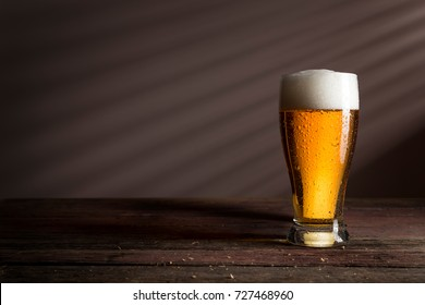 Glass of cold pale beer on a rustic wooden table
