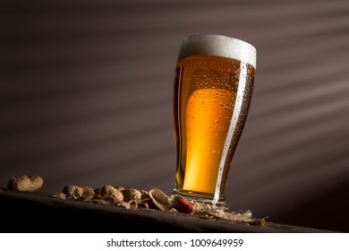 Glass of cold pale beer placed on a burlap coaster and some peanuts on a rustic wooden table