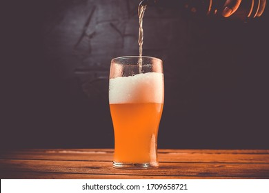 Glass of cold pale beer placed on a rustic wooden table