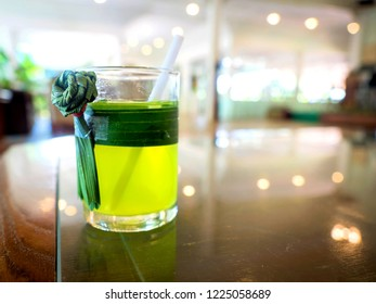 Glass of cold Pandan juice - healthy food against wood,With pandan green on the old wooden floor.