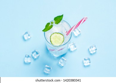 Glass of cold and refreshing water with ice, mint and cucumber on a blue background. Ice Cube. Concept of hot summer, alcohol, cooling drink, thirst quenching, bar. Flat lay, top view