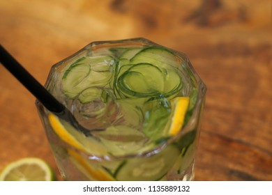 Glass of cold water with fresh mint leaves and cucumber with ice cubes on wooden background.
