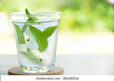 glass of cold water with fresh mint leaves and ice cubes