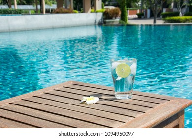Glass of cold water with ice cubes and slice of green lime on wooden table by beautiful swimming pool.