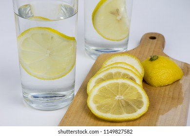 A glass of cold water with lemon on a white kitchen table. A refreshing drink in warm weather. Light background.