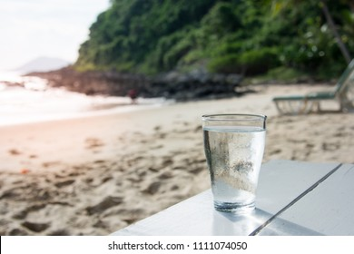 A glass of cold water on white wooden table on the beach. Stay hydrate this summer.