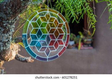 A glass colorful mandala hanging off a tree, with an adobe house in the back.