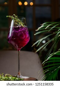 Glass of colorful pink alcohol cocktail with thyme