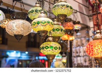 Glass, colorful, traditional, decorative Turkish lamps hang on the ceiling in the store
