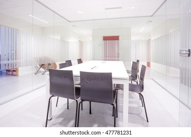 an glass conference room with a table and chairs