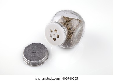Glass container of dried basil on a white surface. Spices isolated on white background.