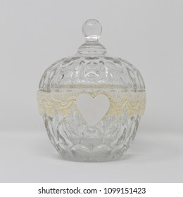 A glass container and lid, decorated by a handmade ribbon and a white wooden heart as an ornament.