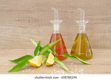 Glass containers with olive oil and vinegar , sea salt, lemon on a wooden background. Traditional greek food.