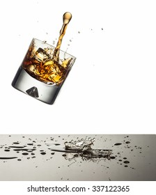 Glass containing ice and liquor falling towards a reflective counter top onto which the spirit is splashing with white background