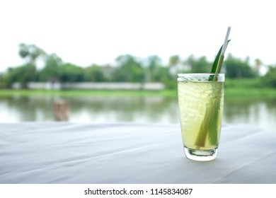A glass contains lemongrass refreshment drink and a straw on a white sheeted table with river background