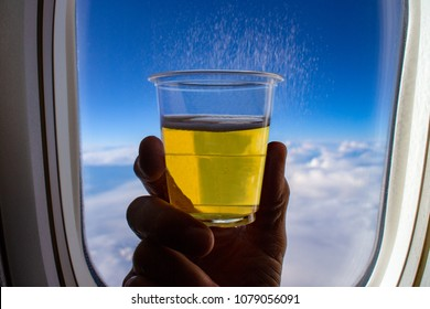 A glass of cool beer, held up in front of an airplane window, with view of clouds and horizon in the background seen through the window